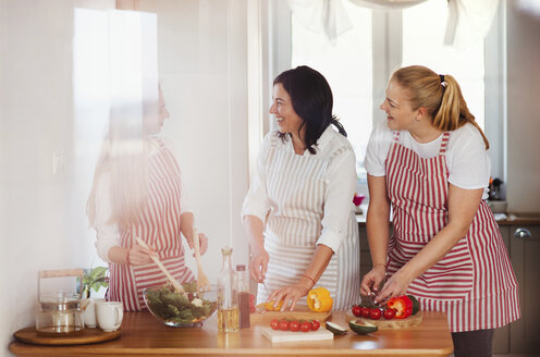 Mother and daughters standing in kitchen, preparing food, chopping vegetables - HAPF02900