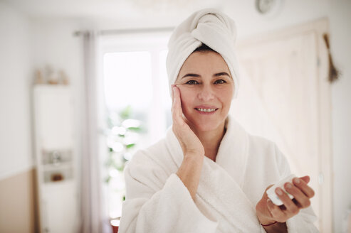 Portrait of mature woman in a bathroom at home applying moisturizer - HAPF02951