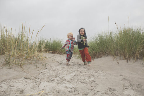Boy and girl running to the beach together - IHF00040