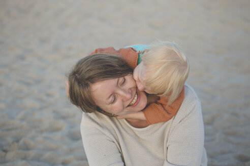 Little girl hugging her mother on the beach - IHF00043