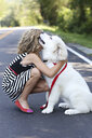 Close up of girl hugging dog on road - BLEF05608