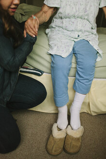 Granddaughter helping grandmother out of bed into slippers - BLEF05681