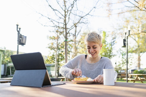 Portrait of smiling woman with digital tablet eating piece of cake outdoors - FBAF00608