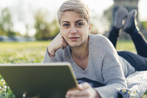 Portrait of young woman lying on a meadow with digital tablet - FBAF00617