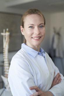 Portrait von Ärztin in Praxis mit Anatomie Model von Wirbelsäule, Studio, München, Deutschland - PNEF01466