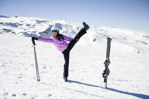Woman wearing ski clothing stretching before skiing at the Sierra Nevada, Andalusia, Spain - JSMF01097