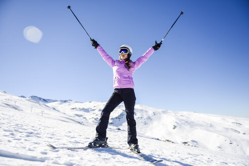 Happy woman raising her ski poles in snow-covered landscape in Sierra Nevada, Andalusia, Spain - JSMF01106