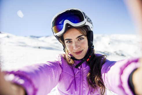 Selfie of young woman in ski clothes in snow covered-landscape - JSMF01112