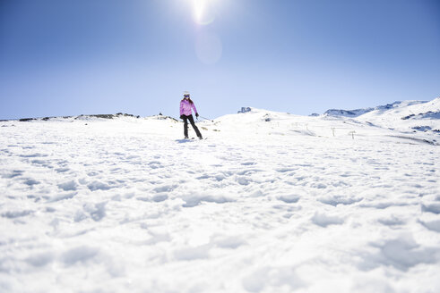 Woman skiing under blue sky, Sierra Nevada, Andalusia, Spain - JSMF01121
