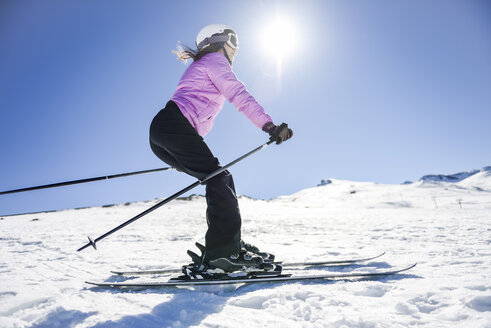 Woman skiing under blue sky, Sierra Nevada, Andalusia, Spain - JSMF01124