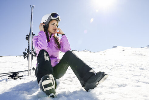 Woman taking a break after skiing sitting on the snowy ground in Sierra Nevada, Andalusia, Spain - JSMF01130