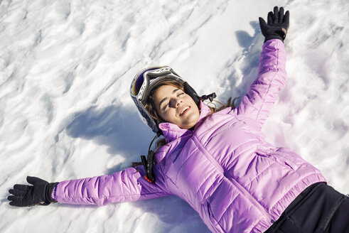 Happy woman taking a break after skiing lying on the snowy ground in Sierra Nevada, Andalusia, Spain - JSMF01139