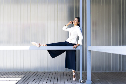 Female ballet dancer during training on a railing, using smartphone - ERRF01443