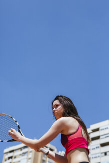 Female tennis player playing on court in the city - LJF00061