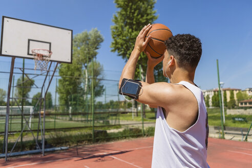 Young man playing basketball, smartphone in arm pocket - MGIF00515