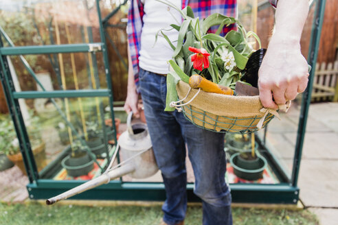 Close-up of man holding basket with flowers and watering can before greenhouse in garden - NMS00320