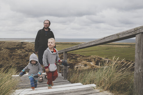 Father and his children walking up  stairs among the dunes, Sylt, Germany - IHF00053