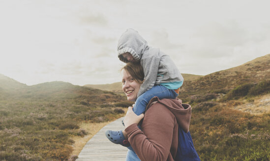 Portrait of smiling mother carrying little daughter on her shoulders, Sylt, Germany - IHF00056