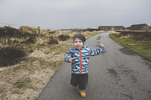 Portrait of little boy running on empty road, Sylt, Germany - IHF00062