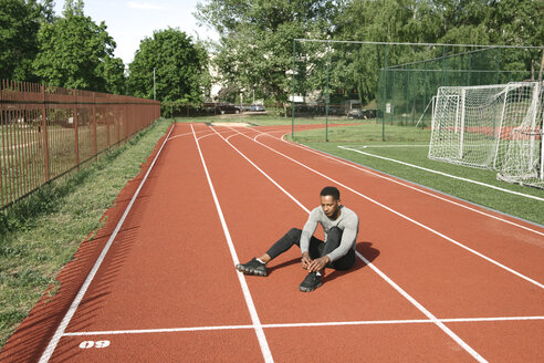 Sportsman sitting on racetrack and tying shoes before workout - AHSF00429