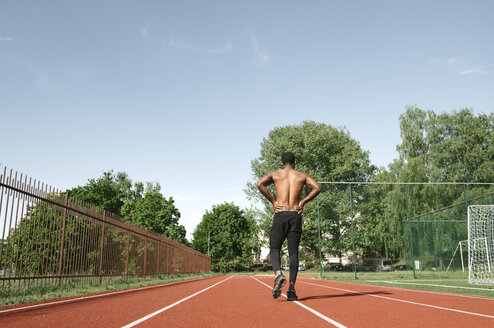 Athletic man walking on rubber racetrack, rear view - AHSF00435