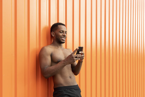 Portrait of athlete using smartphone in front of an orange wall - AHSF00441