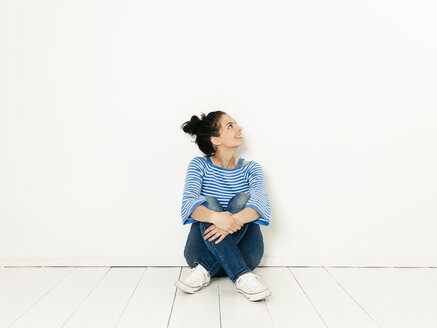 Beautiful young woman with black hair and blue white striped sweater sitting on the ground in front of white background - HMEF00418