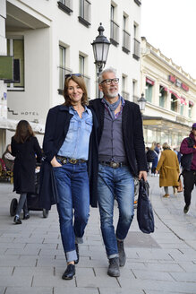 Mature couple walking in the city, with arms around - ECPF00762