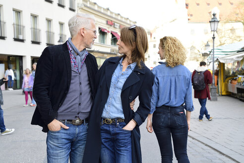 Mature couple walking in the city, man looking after an other woman - ECPF00768