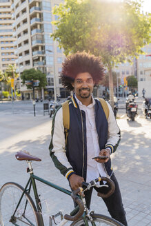 Portrait of smiling casual businessman with bicycle and cell phone in the city, Barcelona, Spain - AFVF03037