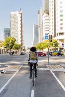 Rear view of casual businessman on bicycle in the city, Barcelona, Spain - AFVF03046