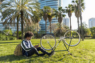 Casual businessman with cell phone and bicycle in urban park, Barcelona, Spain - AFVF03055