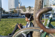 Casual businessman with bicycle using cell phone in urban park, Barcelona, Spain - AFVF03064