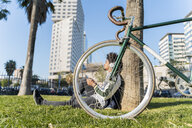 Casual businessman with bicycle taking a break in urban park listening to music, Barcelona, Spain - AFVF03067