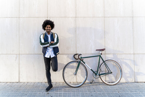Portrait of smiling casual businessman with bicycle standing at a wall - AFVF03127