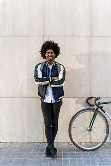 Portrait of smiling casual businessman with bicycle standing at a wall - AFVF03130