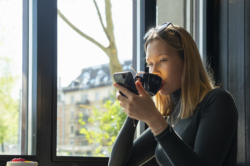 Young woman in a coffee shop drinking coffee while looking at smartphone - FBAF00635