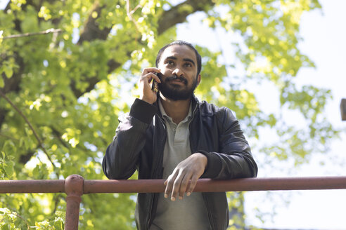 Portrait of bearded young man on the phone outdoors - SGF02377