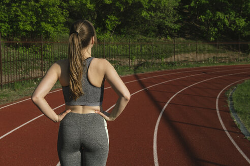 Rear view of sportswoman standing on racetrack - AHSF00475