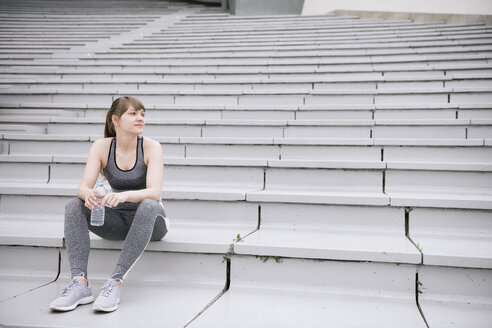 Young woman wearing sportswear sitting on concrete bleachers with a bottle of water - AHSF00484