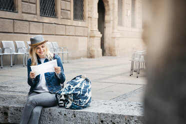 Smiling blond woman with baggage sitting on curb looking at map - HMEF00428