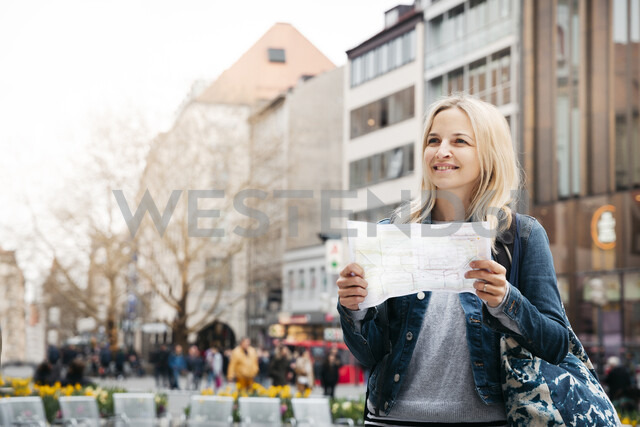 Portrait of smiling blond woman with map and baggage in the city, Munich, Germany - HMEF00431 - Epiximages/Westend61