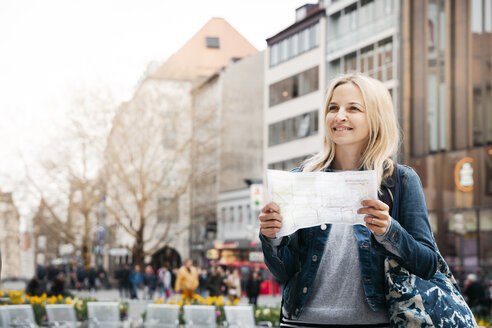 Portrait of smiling blond woman with map and baggage in the city, Munich, Germany - HMEF00431