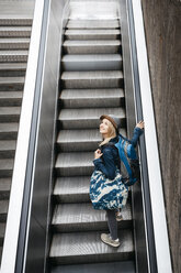 Smiling woman with backpack and travelling bag standing on escalator looking around - HMEF00434