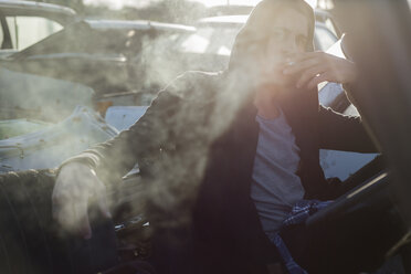 Young man smoking cigarette, sitting in old car in scrapyard - JPTF00080