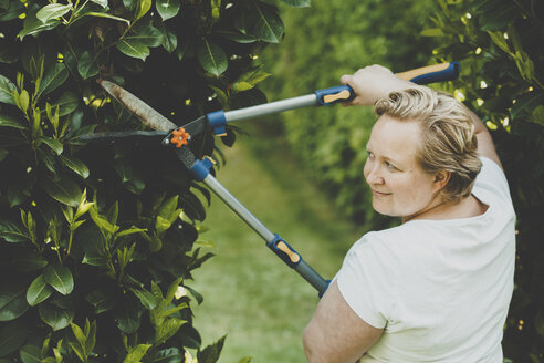 A woman cutting the shrubs with big garden scissors - IHF00072