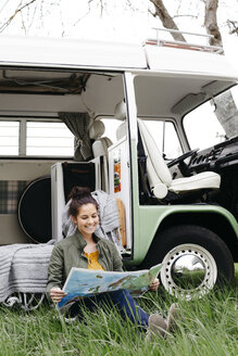Young woman studying map, sitting in the grass, in front of her camper - HMEF00445