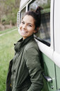Laughing young woman leaning on camper - HMEF00451