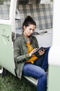 Young woman using digital tablet, sitting in her camper - HMEF00454