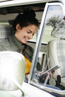 Young woman using digital tablet, sitting in her camper - HMEF00460